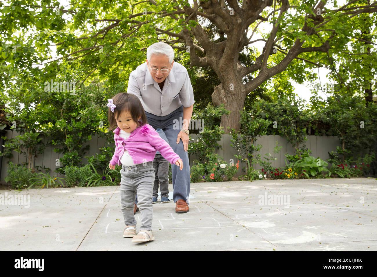 Großvater, Himmel und Hölle mit Kleinkind Enkelin spielen Stockbild