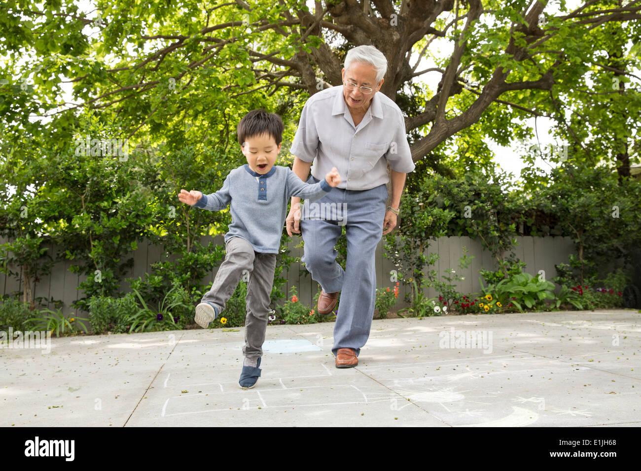 Großvater, Himmel und Hölle mit Enkel spielen Stockbild