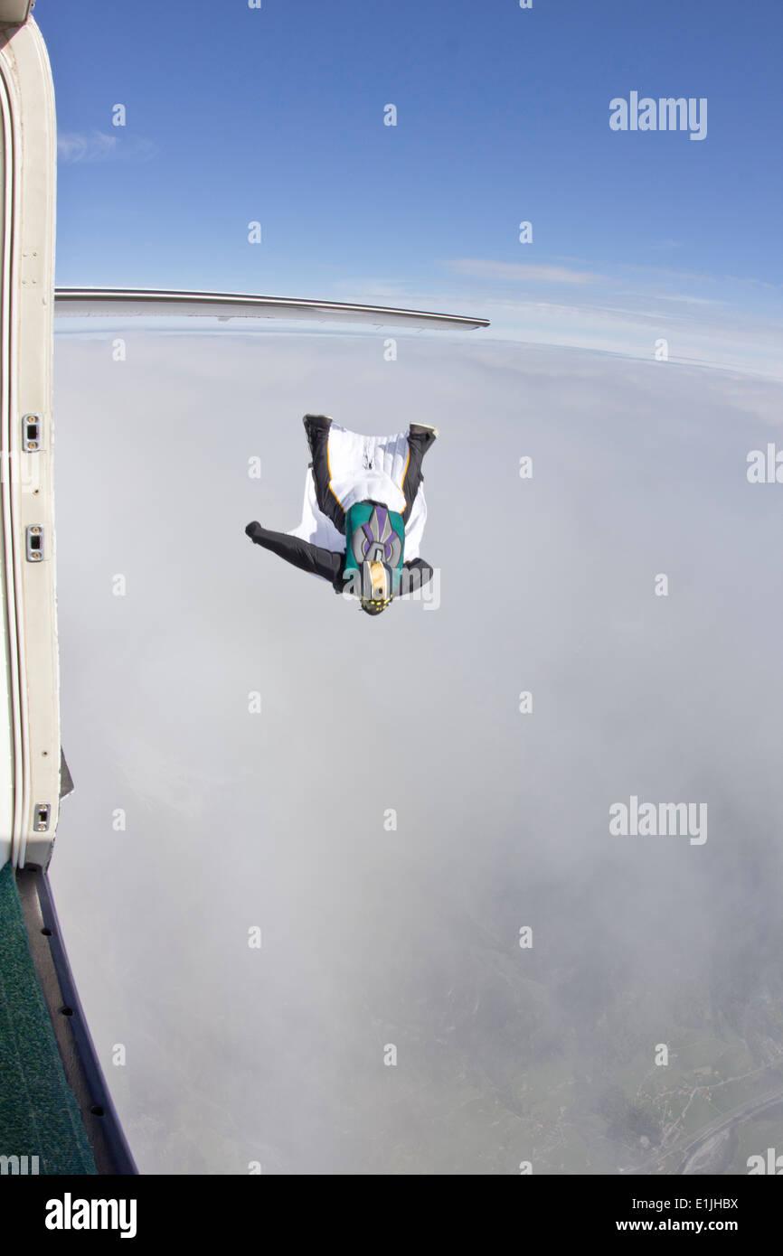 Mitte erwachsenen Mannes über Wolken im Wingsuit fliegen Stockbild