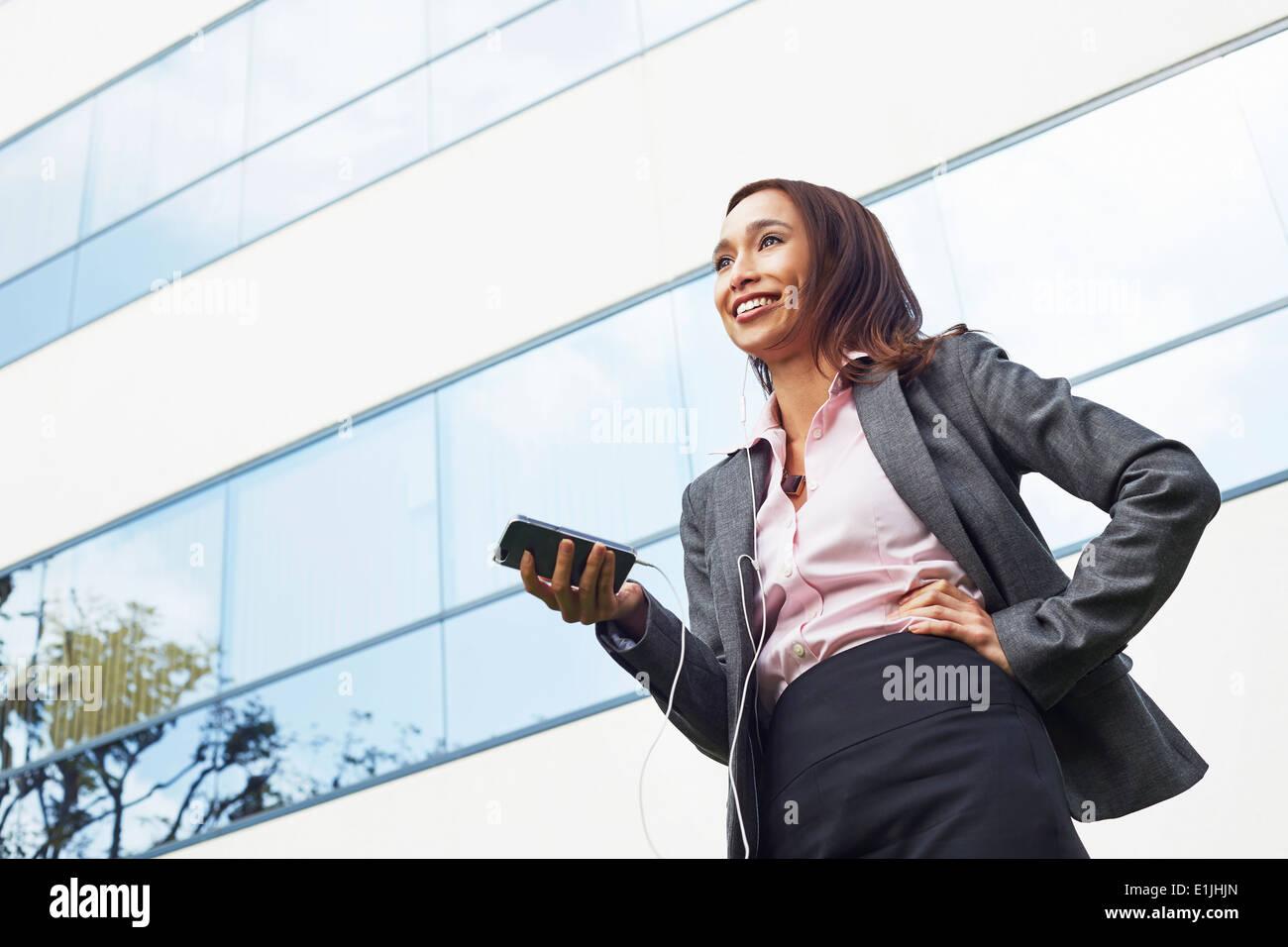 Junge weibliche Unternehmerin mit Smartphone außerhalb Büro Stockfoto