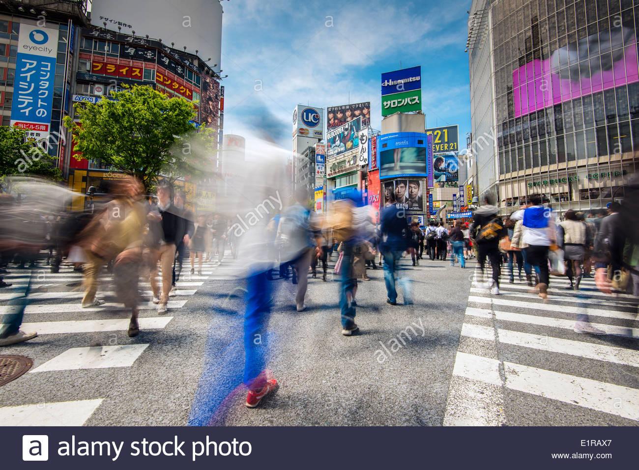 Verschwommene Fußgänger überqueren die Straße an der Kreuzung Shibuya, Tokyo, Japan Stockbild