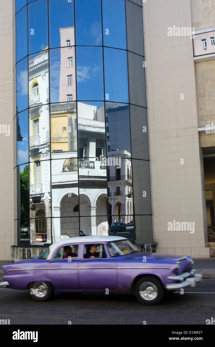 Alte amerikanische Autos reflektiert in abgewinkelten Glasbau, Havanna, Kuba Stockbild