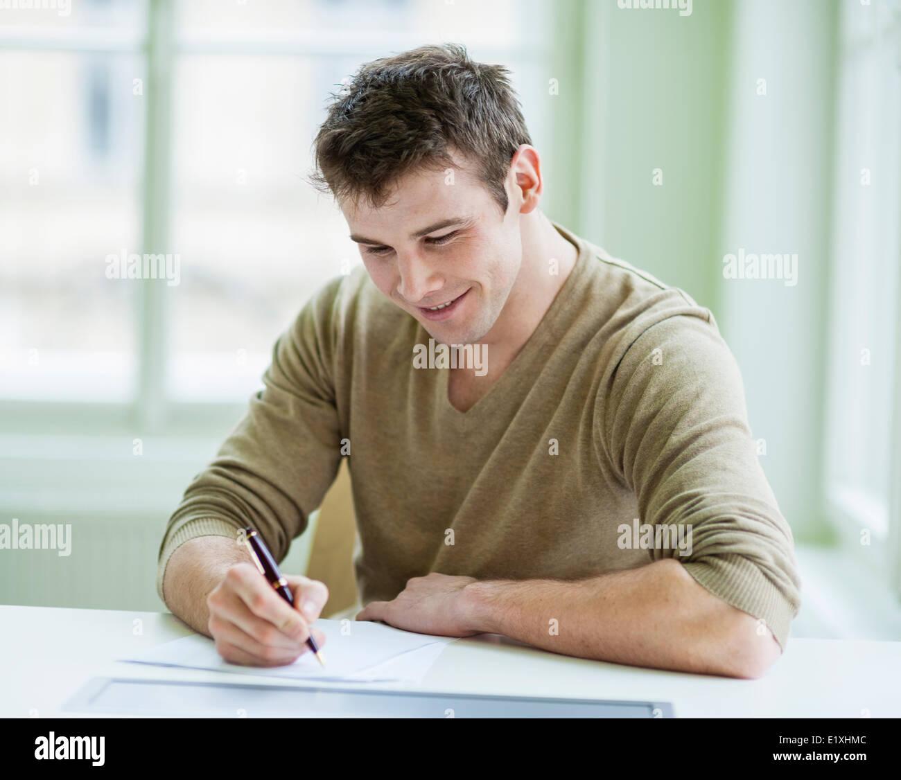 Gut aussehend Geschäftsmann auf Dokument am Schreibtisch im Büro schreiben Stockbild