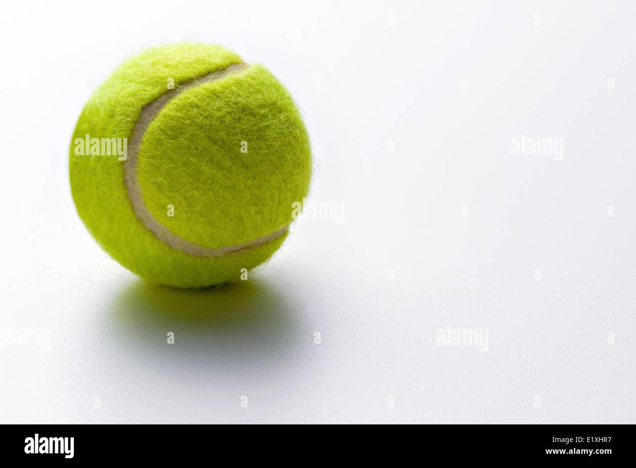 Einzelne gelbe grünen Tennisball auf einem weißen Hintergrund mit textfreiraum konzeptionellen Bewegung, Stockbild