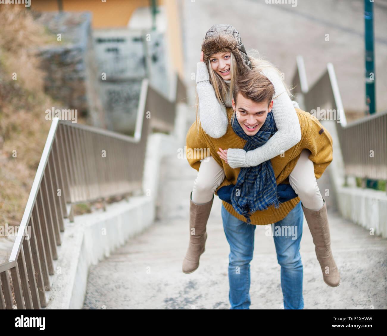 Porträt der lächelnde Frau wird von Mann auf Treppe piggybacked Stockbild