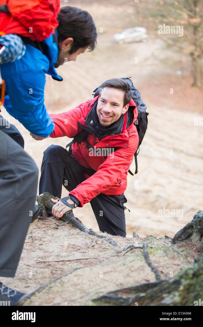 Wanderer, die helfen, Freund beim Wandern im Wald Stockfoto