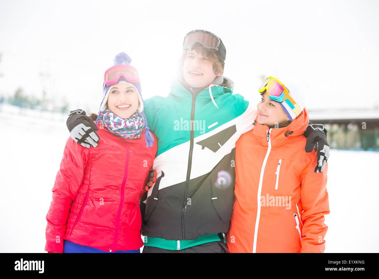 Junger Mann mit Freundinnen stehen Arm um im Schnee Stockfoto