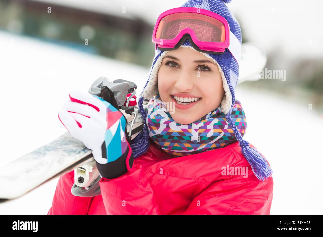 Schöne junge Frau mit Skiern im Schnee Stockbild