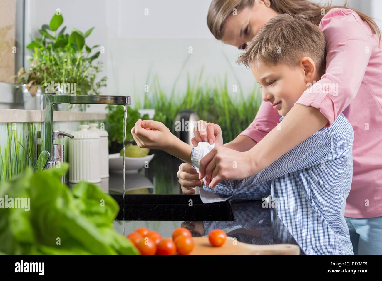 Mutter Unterstützung Sohn beim Falzen Ärmel beim Händewaschen in Küche Stockbild