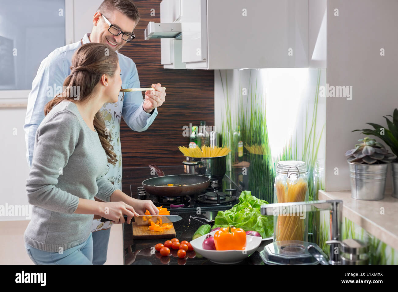 Glücklicher Mann, die Verfütterung von Nahrungsmitteln an Frau Schneiden von Gemüse in der Küche Stockbild