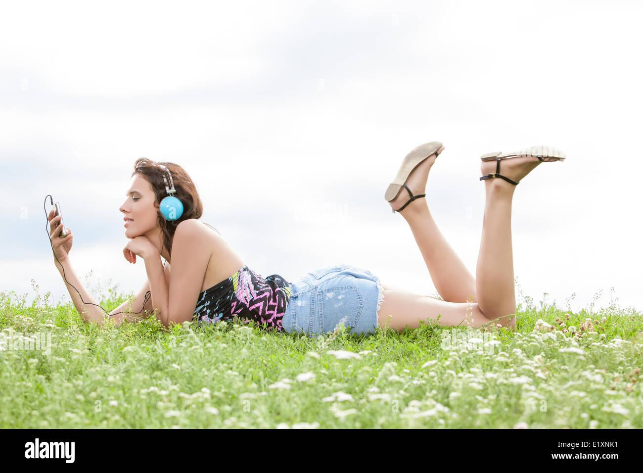 Profil-Schuss von Frau anhören von Musik über Kopfhörer beim liegen auf dem Rasen gegen Himmel Handy Stockbild