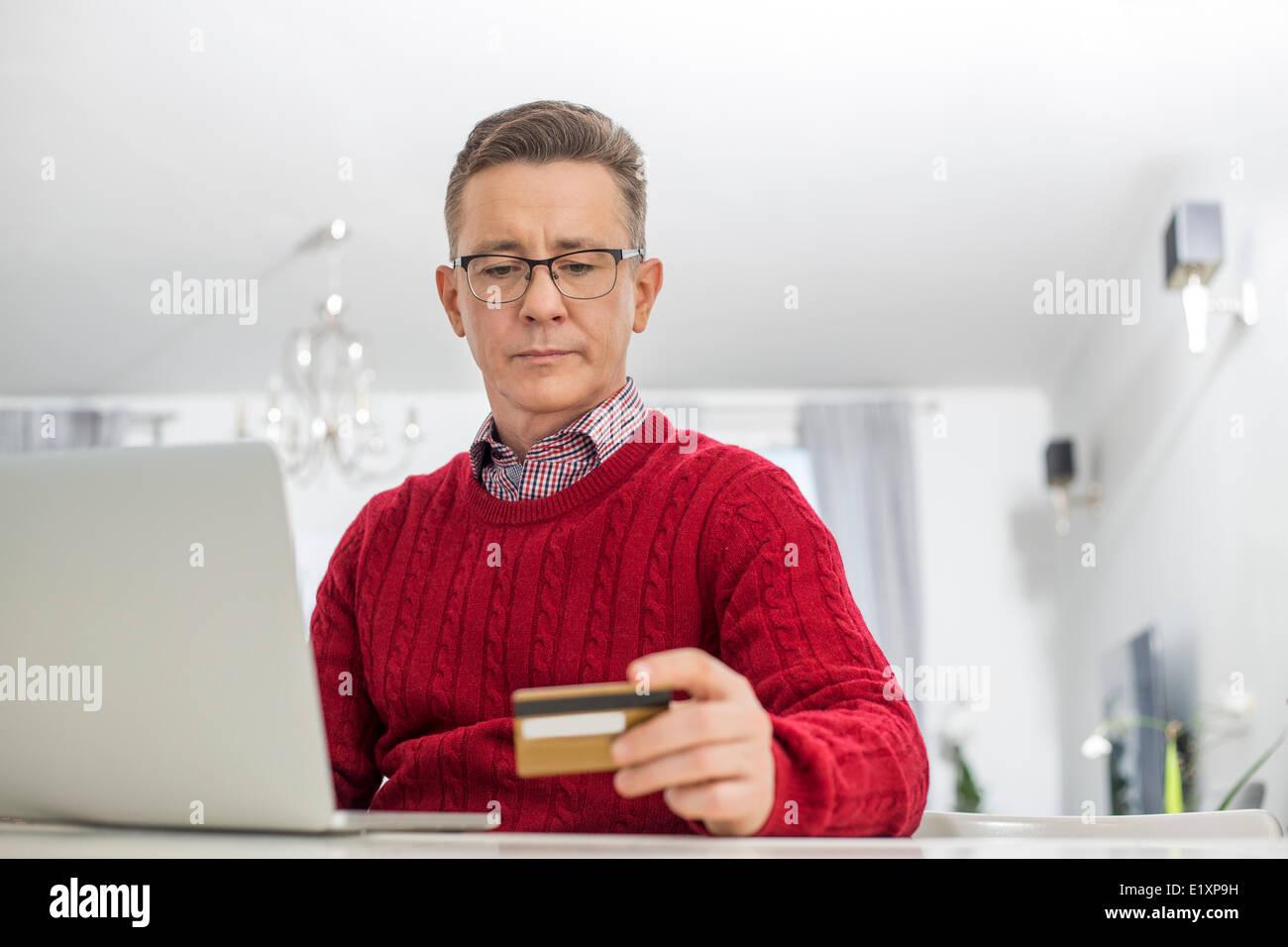 Reifer Mann mit Kreditkarte und Laptop zum Online-shop zu Hause Stockbild