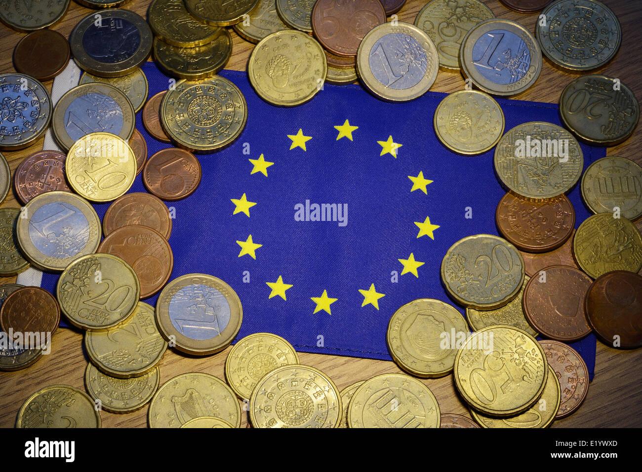 Euro-Münzen und eine EU-Flagge Stockbild
