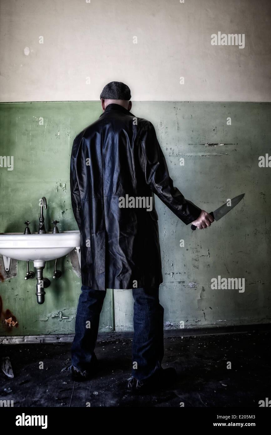 ein Mann in dunkler Kleidung mit einem Messer in einem verlassenen Haus Stockbild