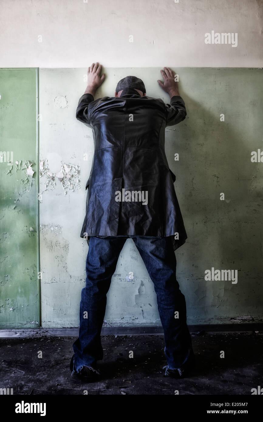 ein Mann in dunkler Kleidung lehnt gegen eine Wand in einem verlassenen Haus Stockfoto