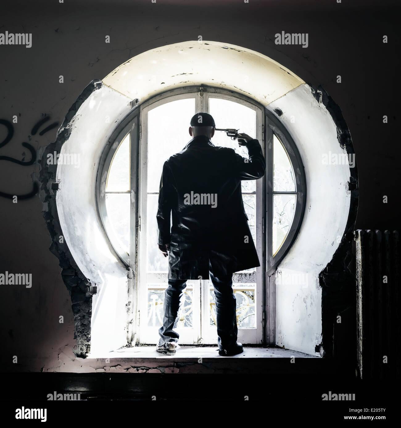 ein Mann mit einem Gewehr vor einem alten Fenster in einem verlassenen Gebäude dreht sich Stockbild