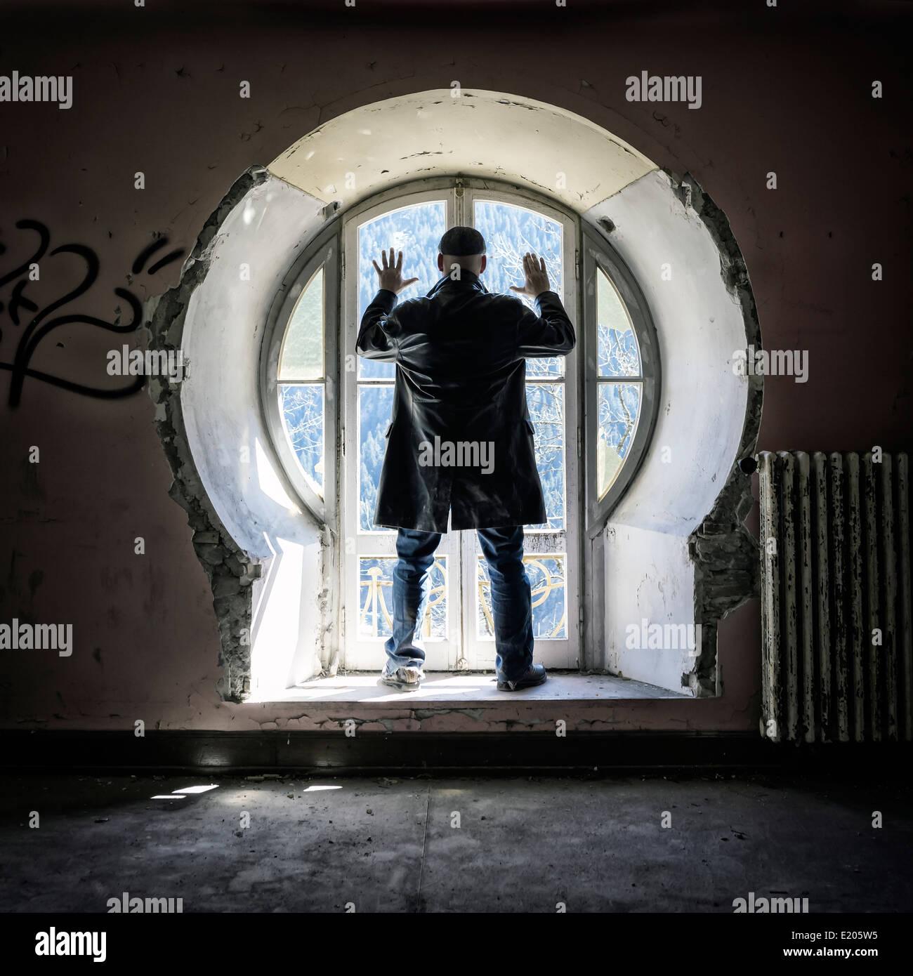 ein Mann vor einem alten Fenster in einem verlassenen Gebäude Stockbild