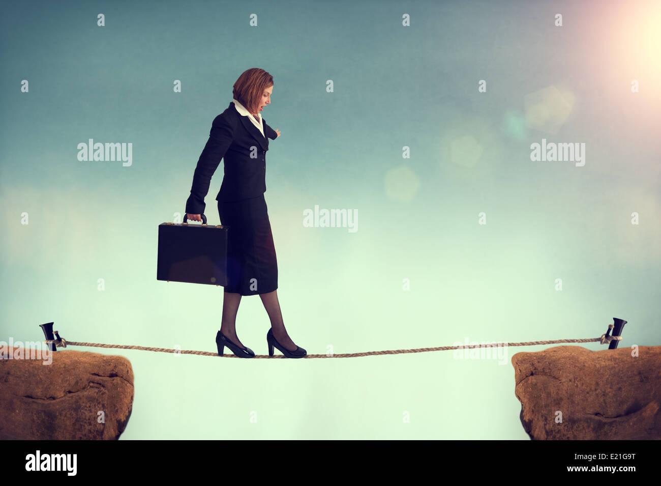 Geschäftsfrau, balancieren auf einem Drahtseil mit Blick auf eine Herausforderung oder Risiko oder Eroberung Stockbild