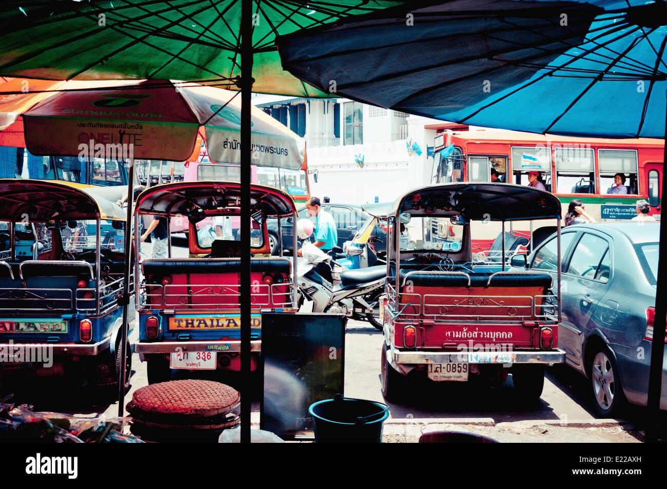 typische Tuk Tuk Taxis geparkt und Verkehr auf der Straße neben Grand Palace in Bangkok Stockbild
