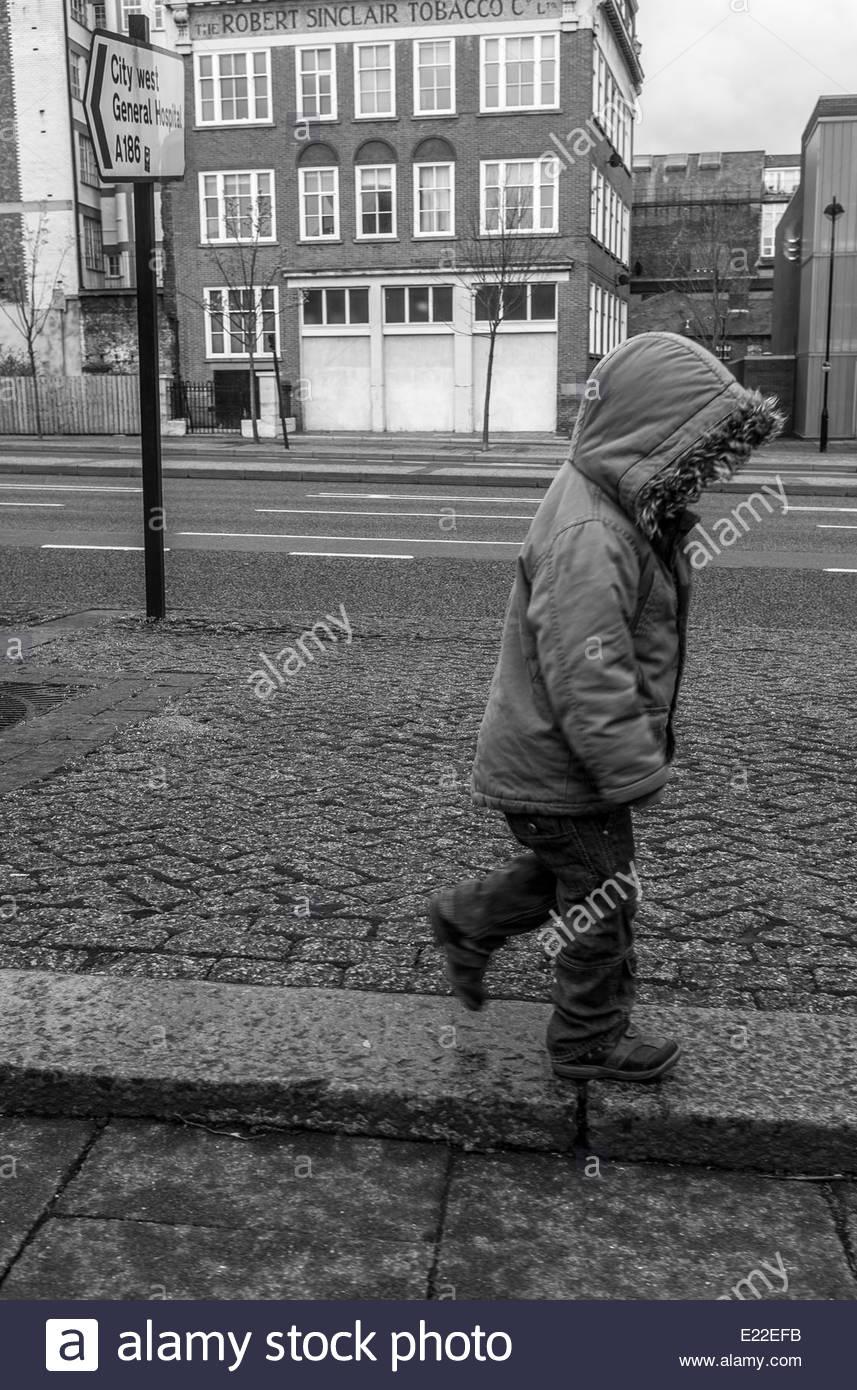 Ein Kind allein zu Fuß entlang einer Stadtstraße Stockbild