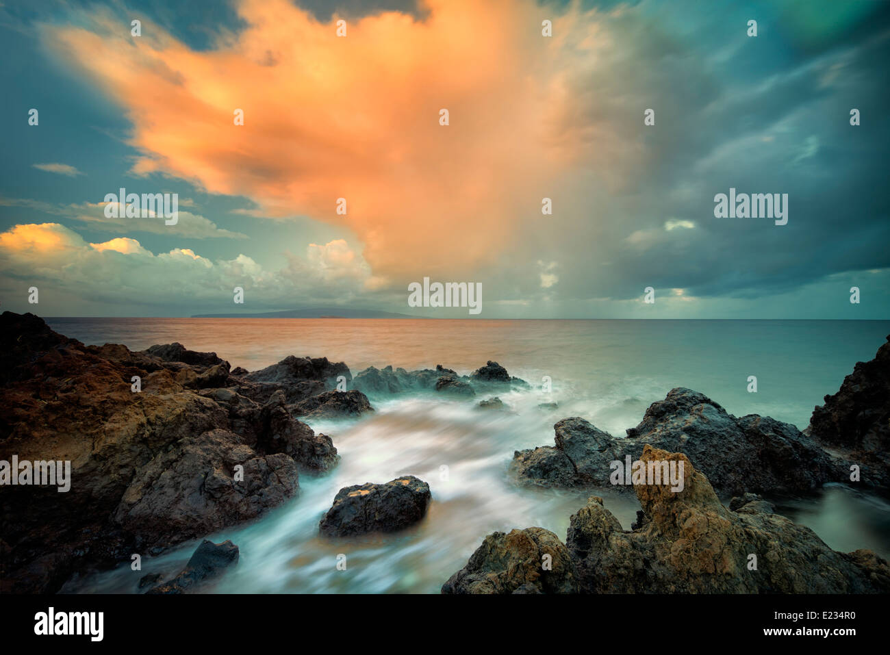 Sunrise und Wolken am felsigen Strand. Maui, Hawaii Stockbild