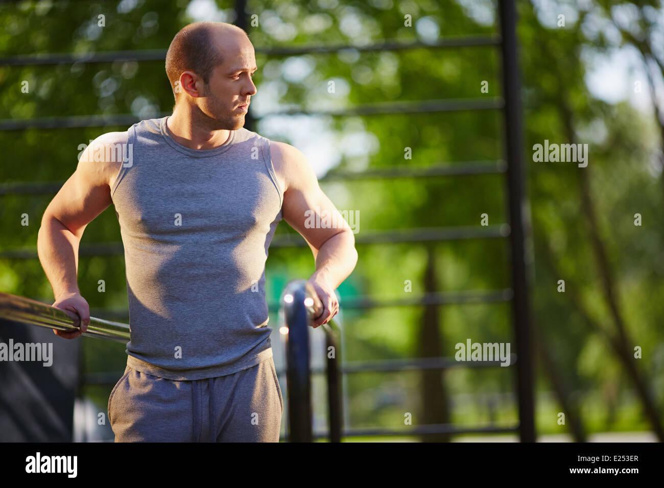 Junger Mann Training auf Sportausrüstung außerhalb Stockbild