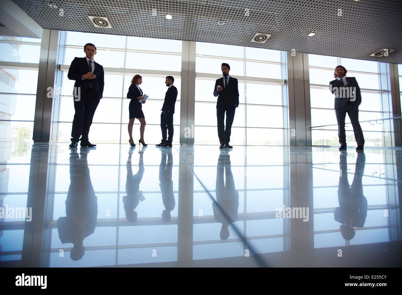 Silhouetten von mehreren Büroangestellte am Fenster stehen und arbeiten Stockbild