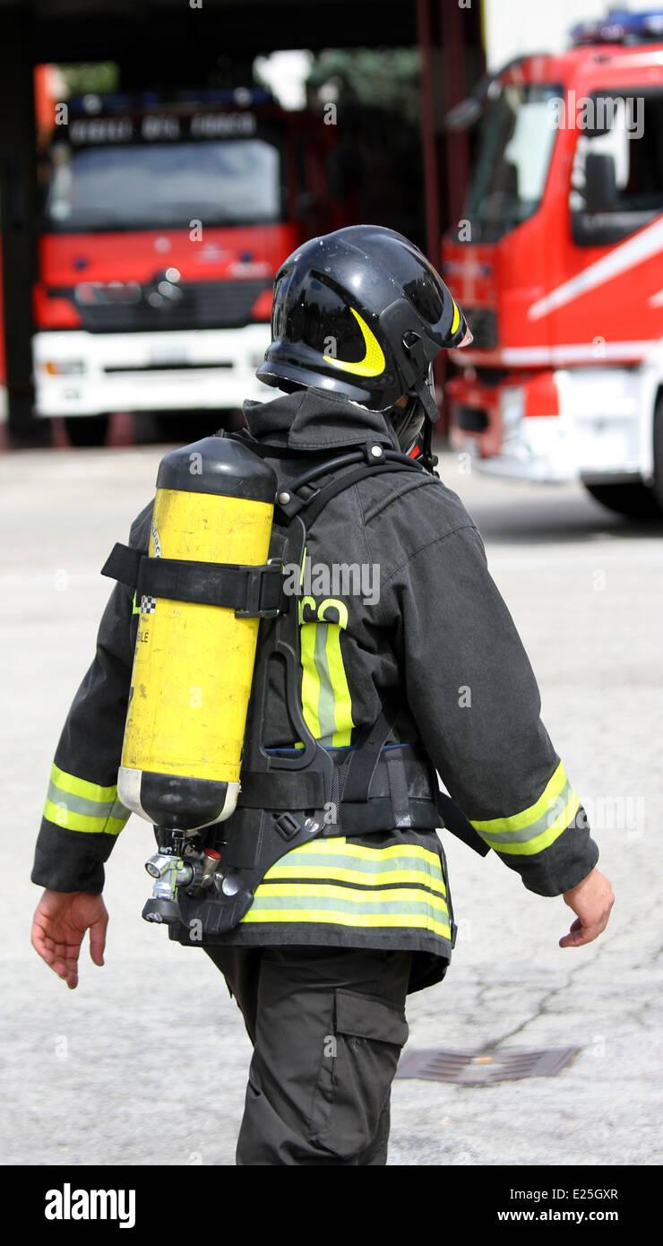 mutiger Feuerwehrmann mit gelben Sauerstoffflasche und der Helm geht auf das Feuer Stockbild