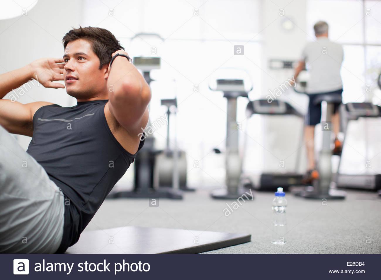 Lächelnder Mann Sit in gymnasium Stockbild