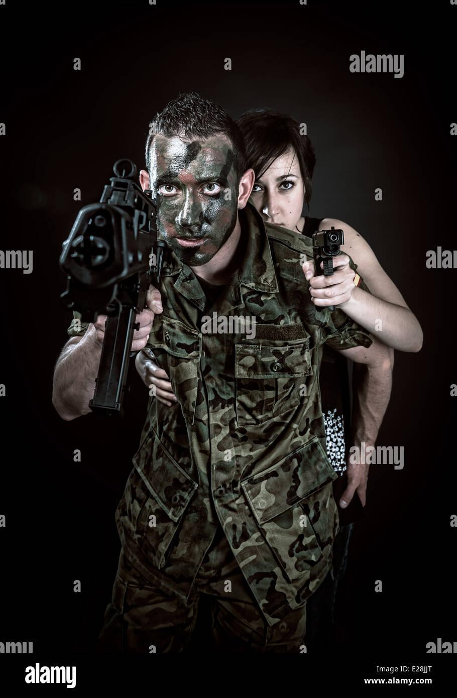 Spanischer Militär mit SMG und Mädchen mit Pistole auf schwarzem Hintergrund Stockbild