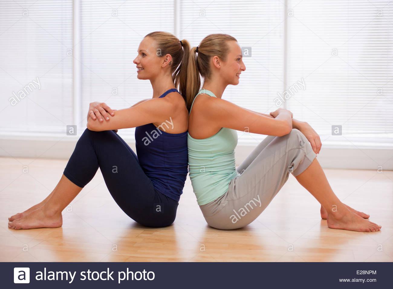 Porträt von lächelnden Frauen sitzen Rücken an Rücken im Fitness-studio Stockbild