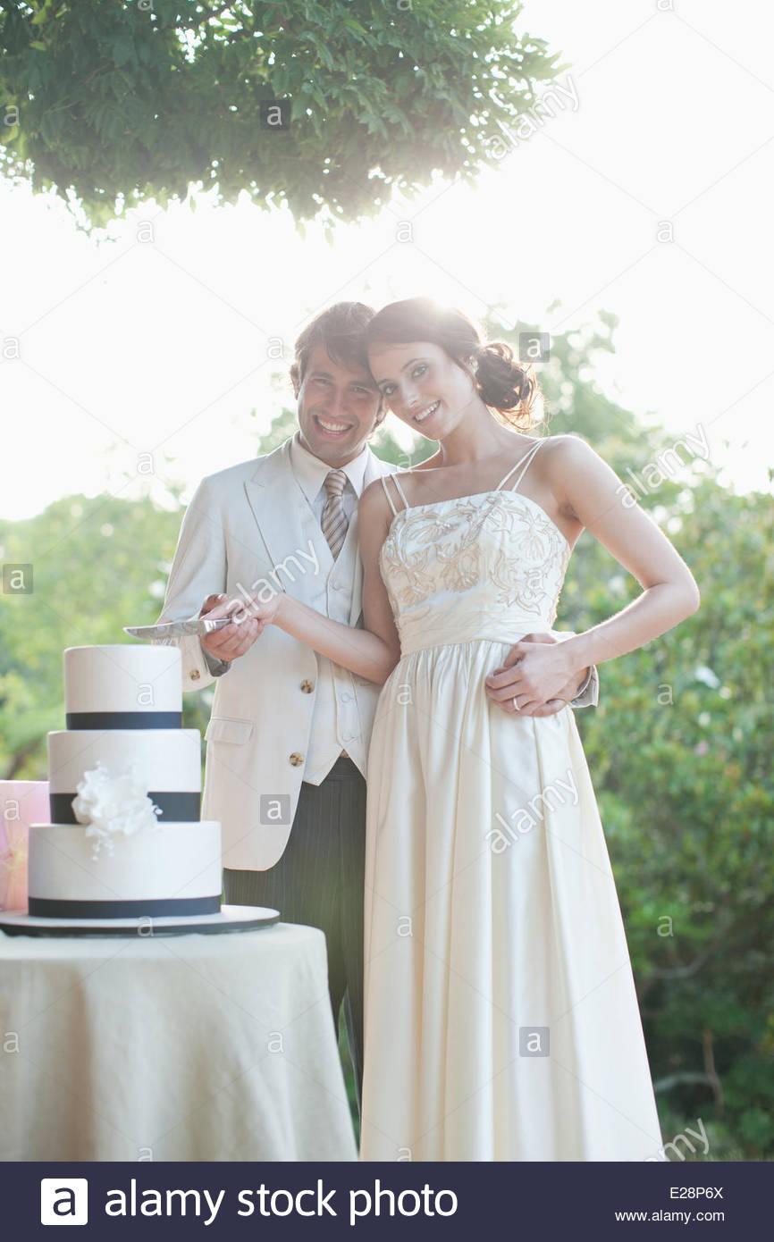 Braut und Bräutigam schneiden Hochzeitstorte Stockbild