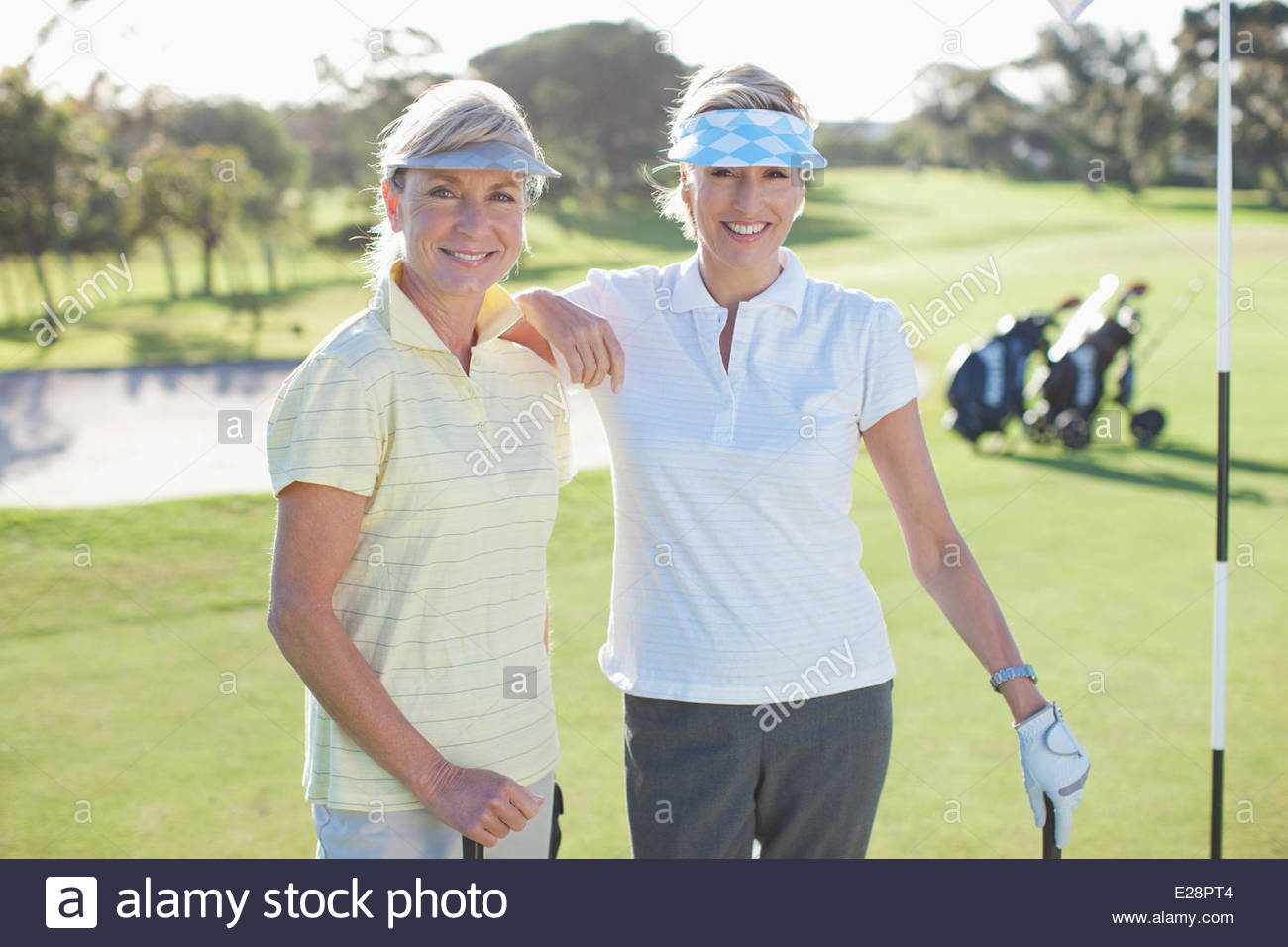 Freunde posieren auf Golfplatz Stockbild