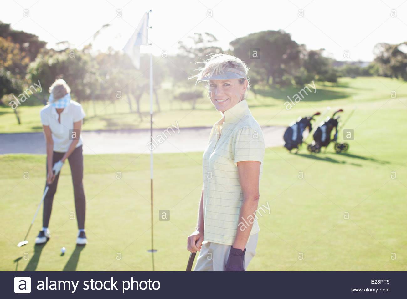 Frau posiert auf Golfplatz Stockbild