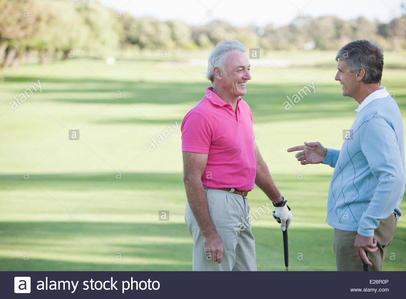 Männer sprechen auf Golfplatz Stockbild