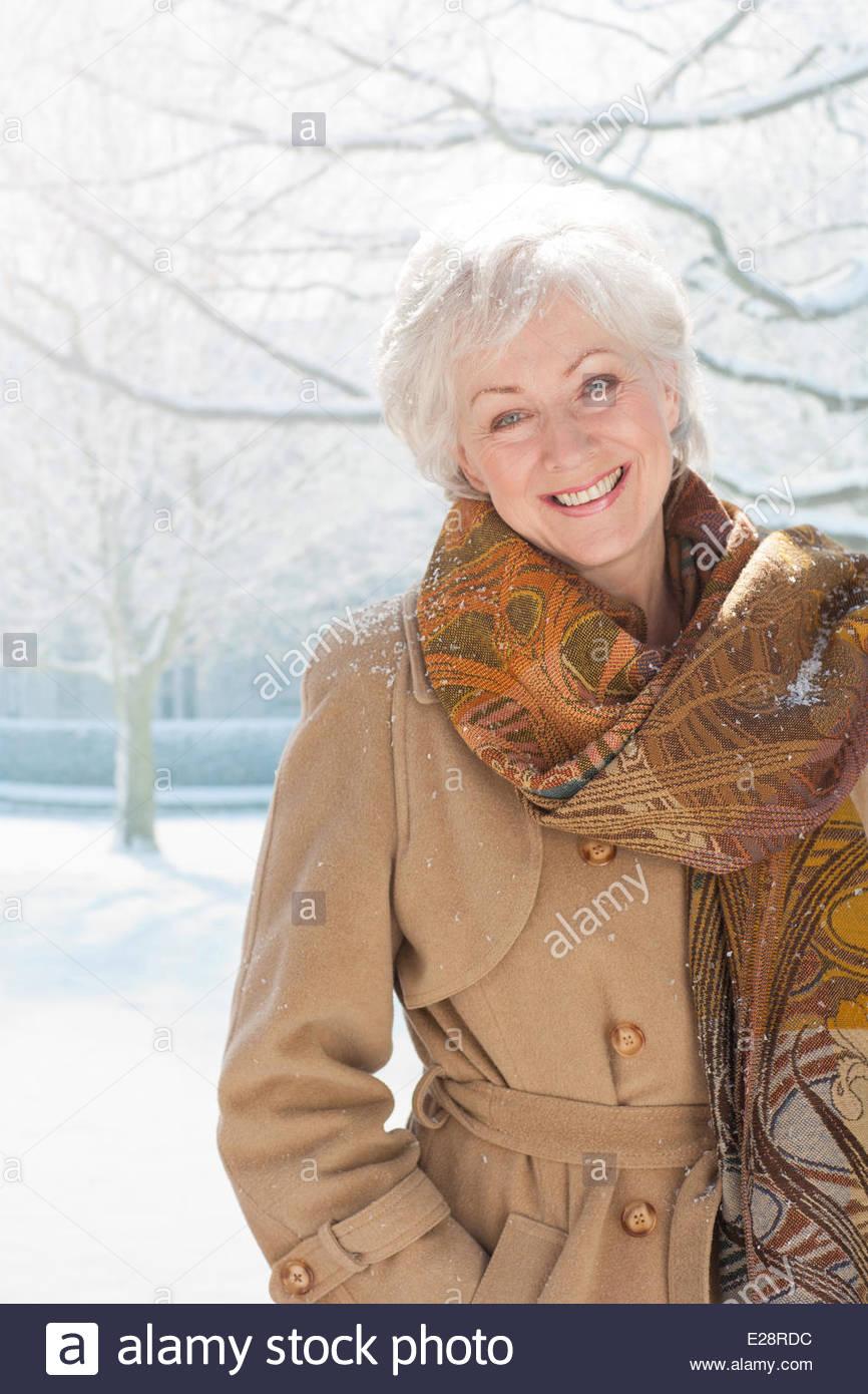 Schnee fällt auf lächelnde Frau Stockbild