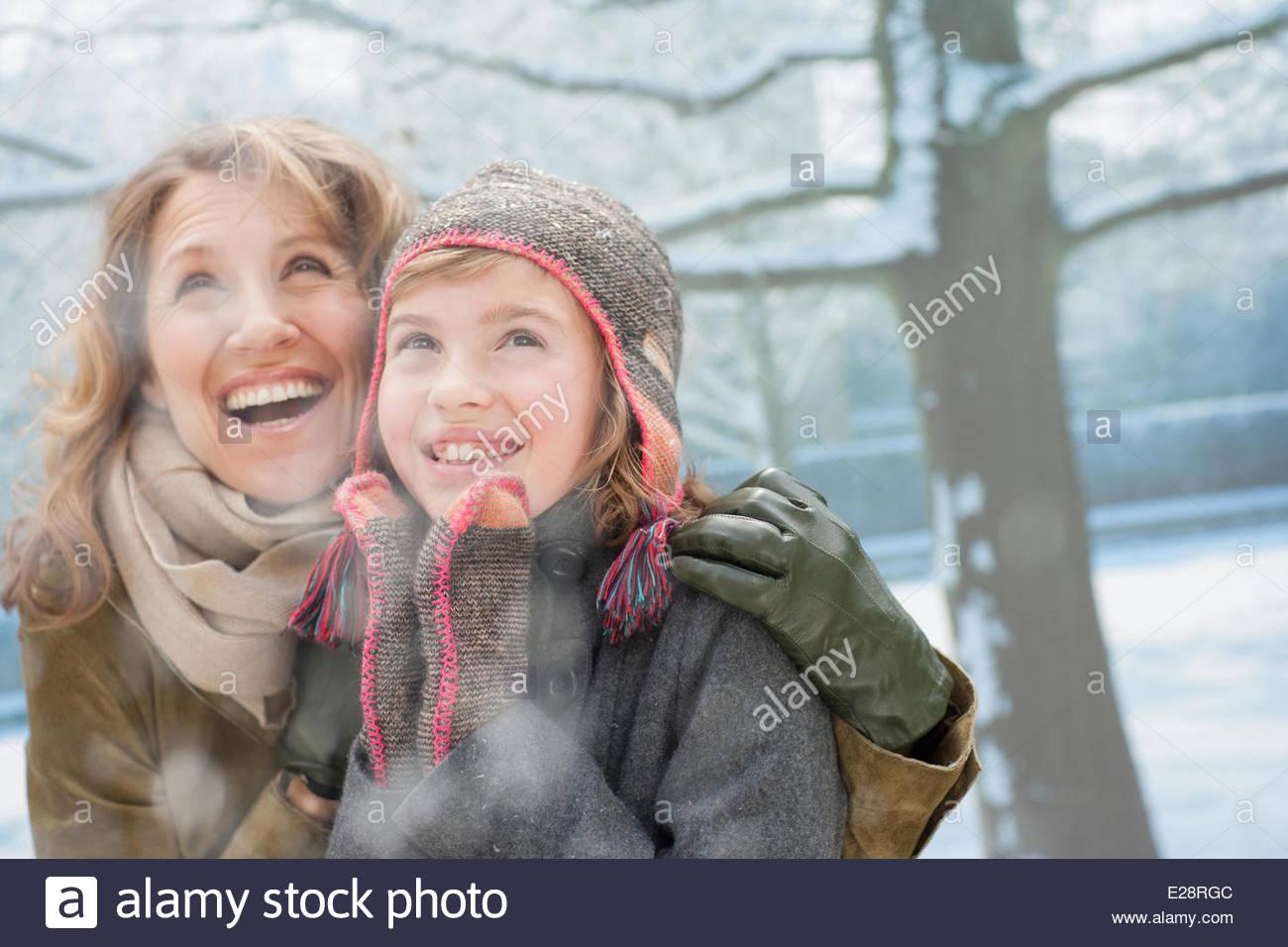 Schnee fällt auf die lächelnde Mutter und Tochter Stockbild