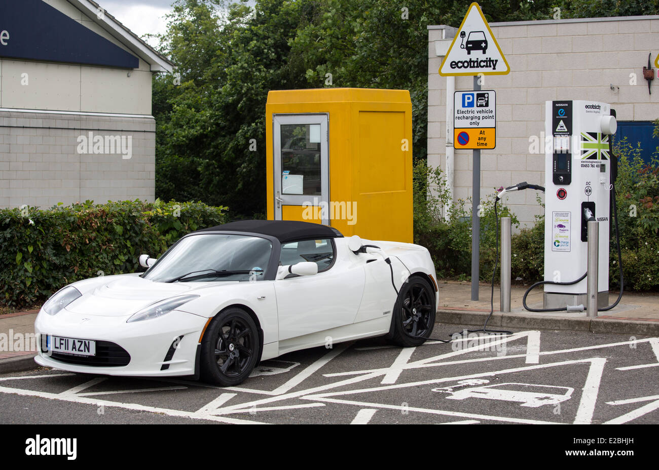 Tesla Roadster Elektroauto Supersportwagen bei Aufladung Heston Dienstleistungen.   Batterie-Elektro-Fahrzeug (BEV) Stockbild