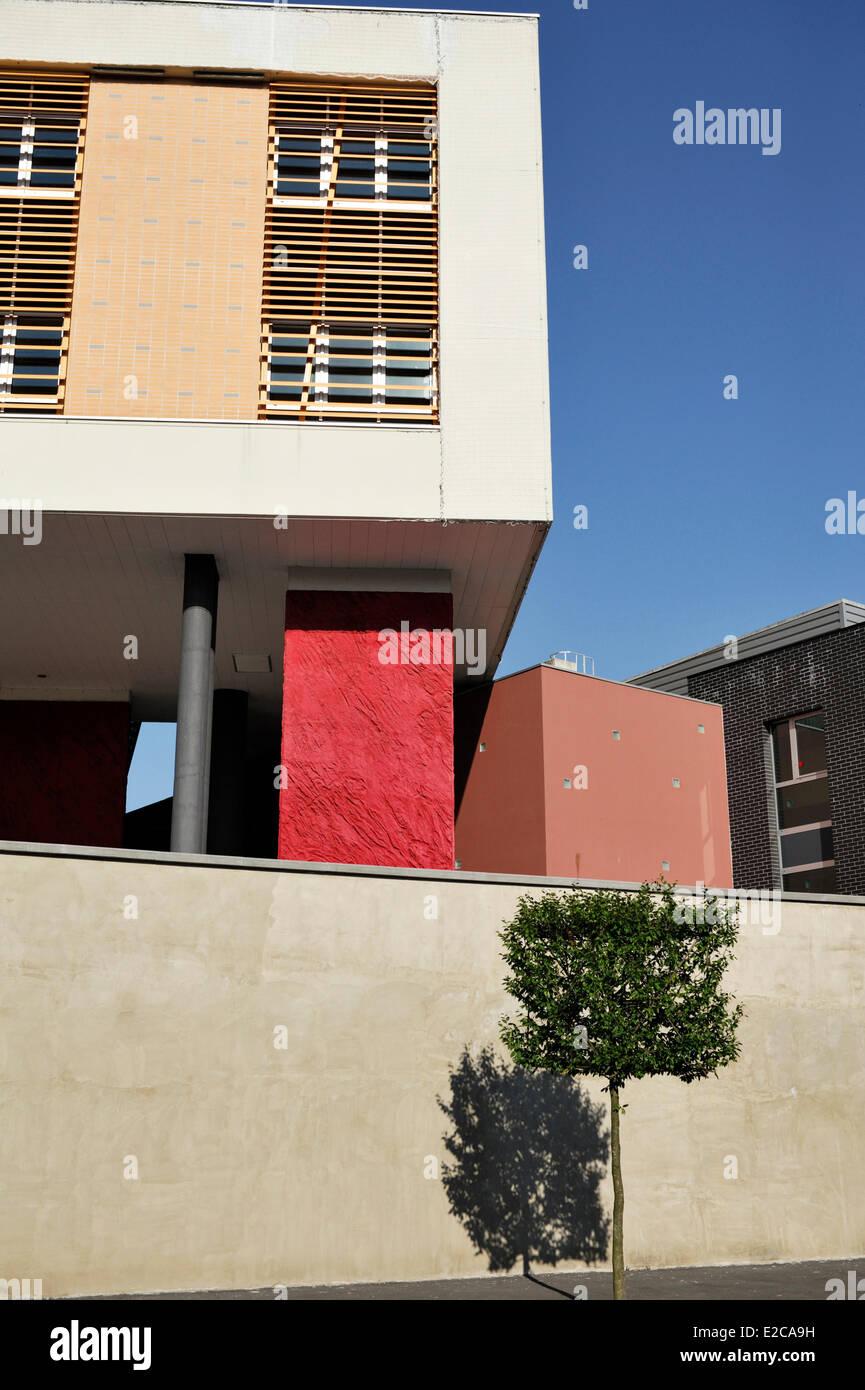Frankreich, Le Cateau-Cambrésis, Nord-Strauch wächst vor der rot-Beige Fassade eines modernen Gebäudes Stockfoto