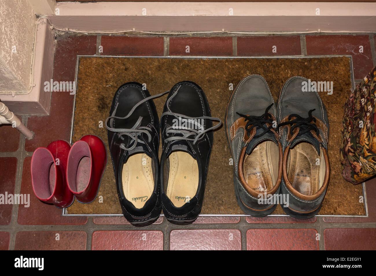 Schuhe und kleine Gummistiefel auf Tür Mat studio Stockbild