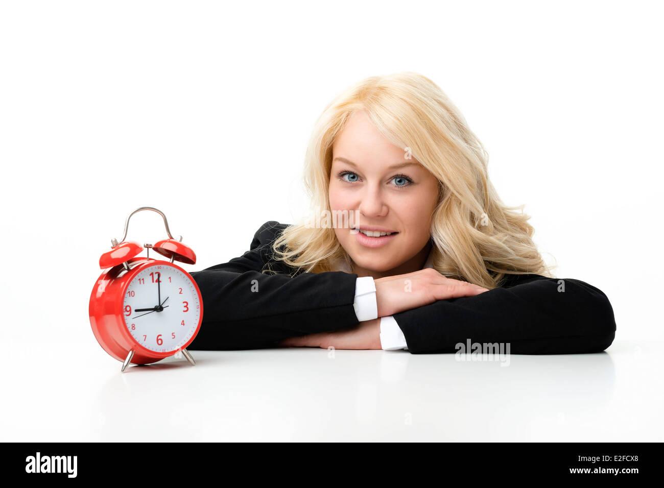 Blonde Frau mit roten Wecker lachen Stockbild