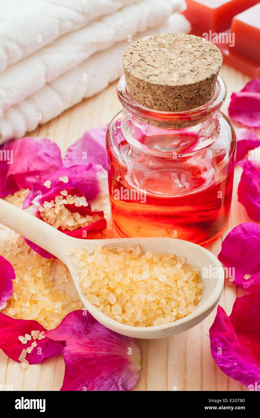 ätherisches Öl in Glasflasche, Meersalz, Handtuch und Rosenblüten Stockfoto