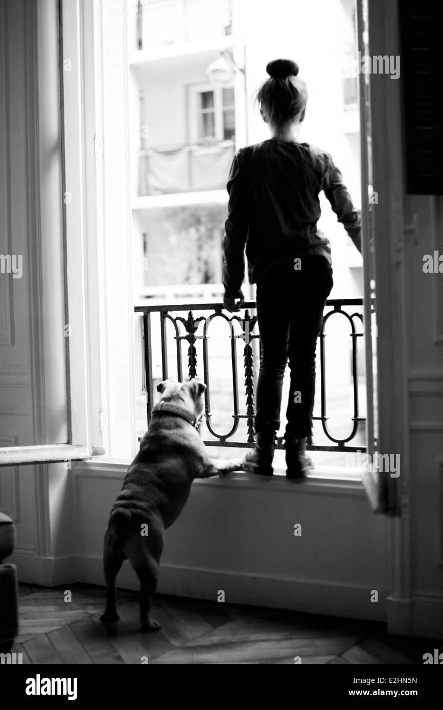 Mädchen stehen auf der Fensterbank mit Hund, beide mit Blick Stockbild