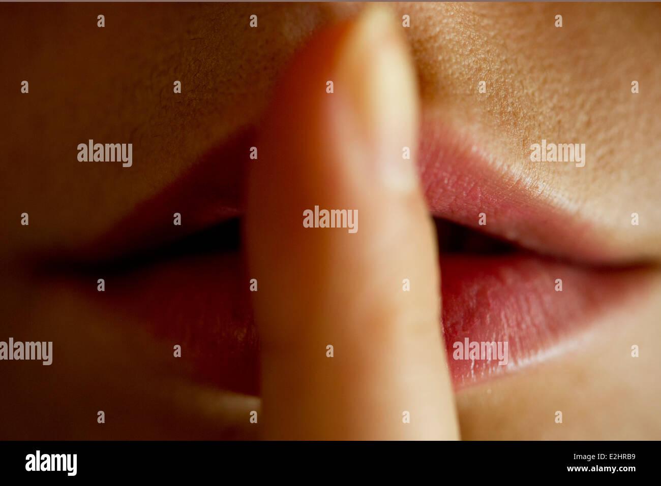 Frau mit Finger auf die Lippen Stockbild