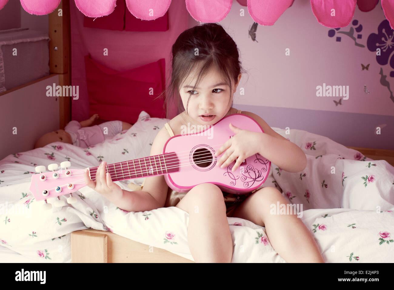 Kleines Mädchen sitzt auf dem Bett, Spielzeug Gitarre spielen Stockbild