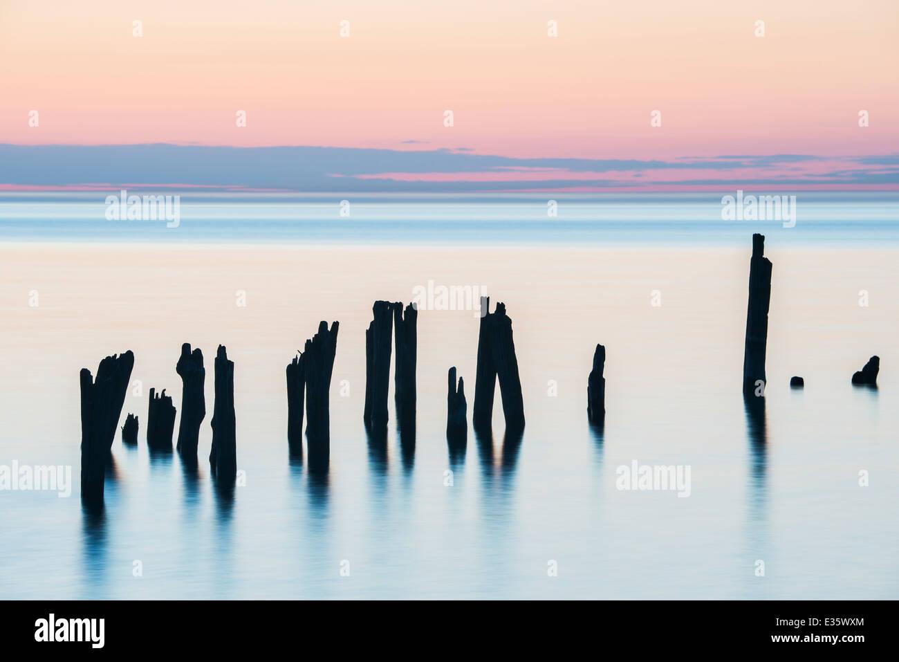 Schattenhafte Figuren, Reste der Dock Pilings halten Sie ruhig in den großen See Lake Huron, Michigan, USA. Stockbild