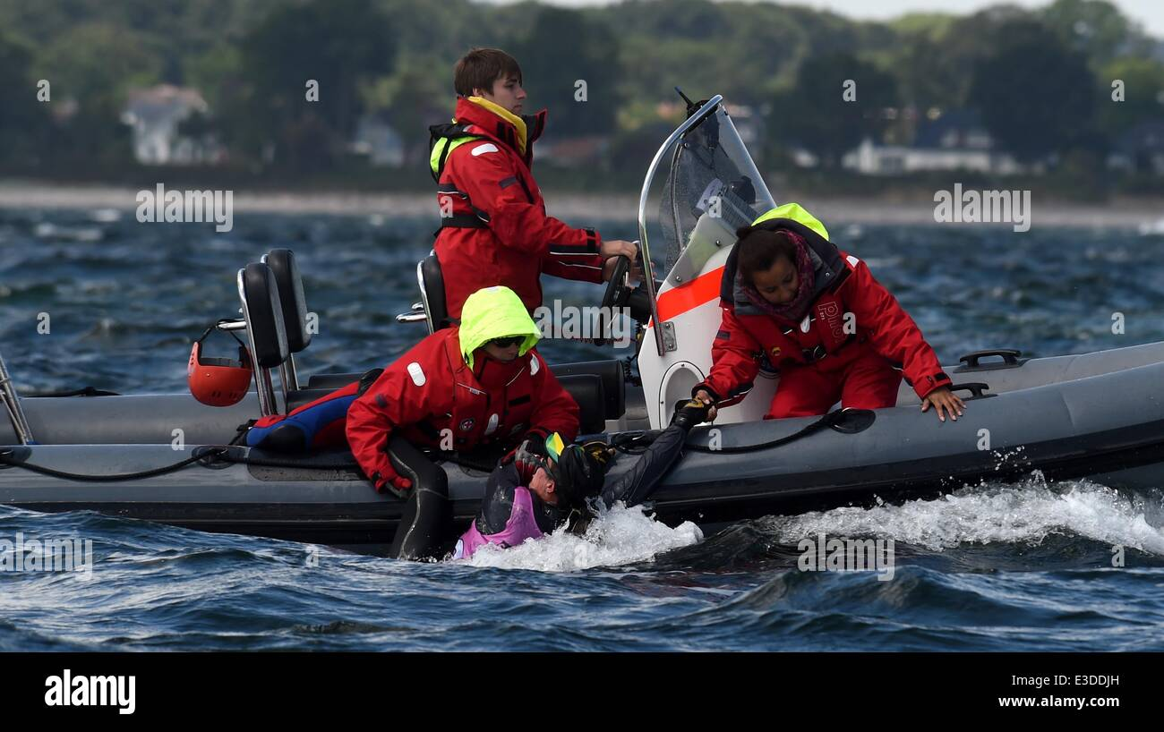 Helfer ziehen eine Seglerin aus dem Wasser während einer Klasse 470 ...