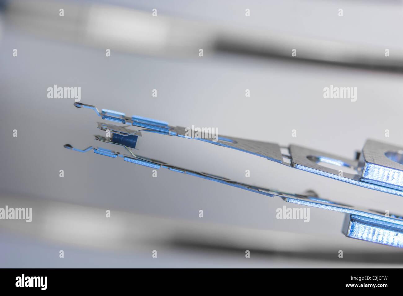 Makro Foto von HDD-Schreib-Lese-Kopf und Arm ruht auf Platte. Visuelle Metapher für das Konzept der Datensicherheit, Stockbild