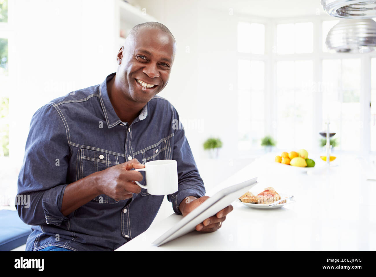 Afrikanische Amerikaner mit Digital-Tablette zu Hause Stockbild
