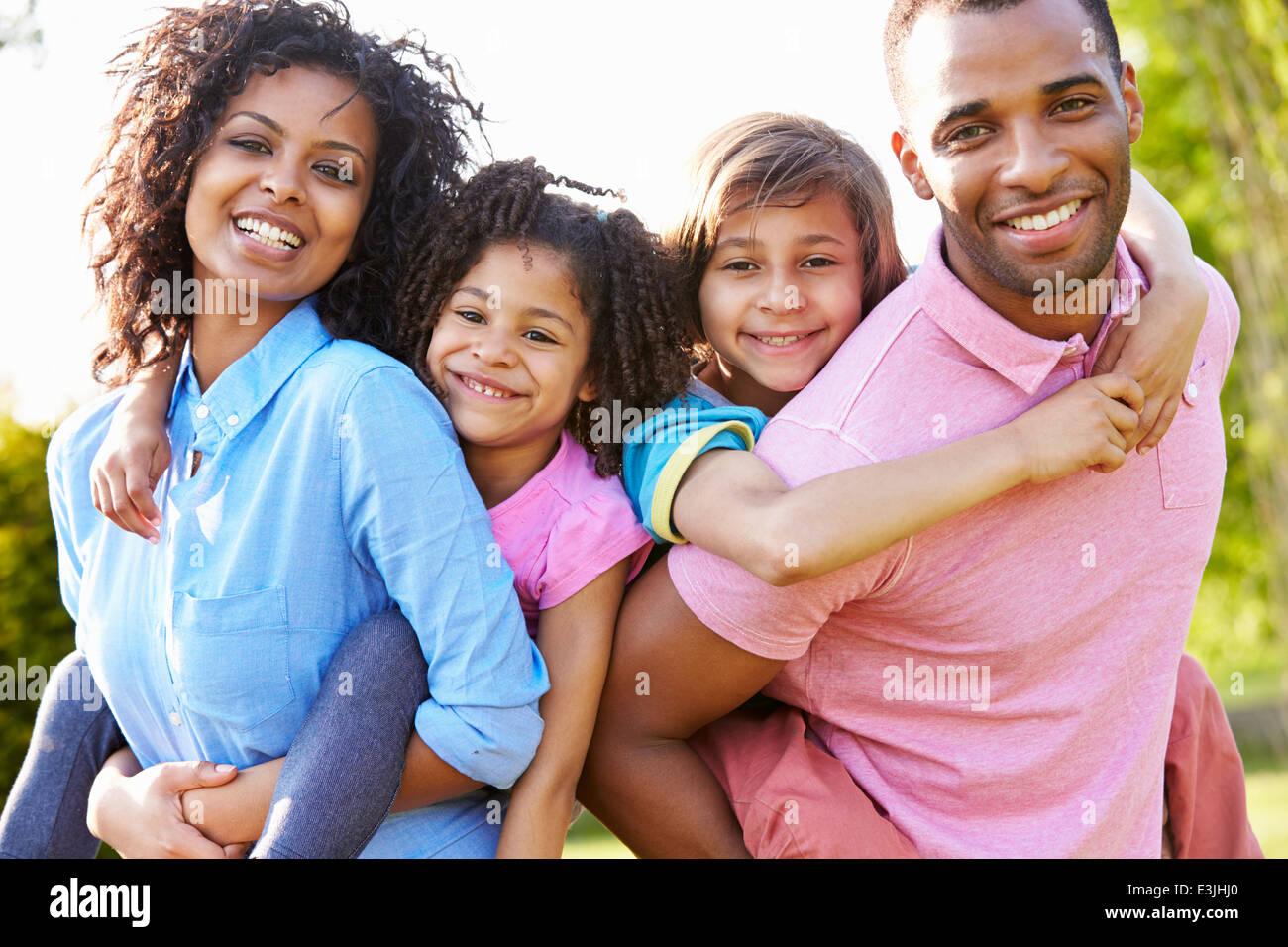 Afrikanische amerikanische Eltern den Kindern Huckepack-Fahrten Stockfoto